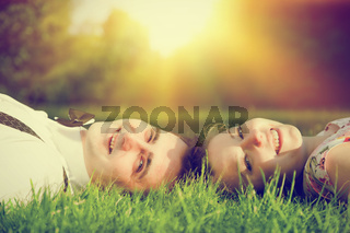 Happy couple in love smiling while lying on summer grass