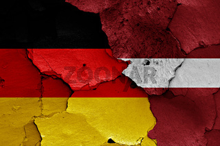 flags of Germany and Latvia painted on cracked wall