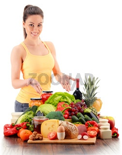 Young woman with variety of organic grocery products isolated on white