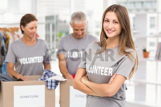 Smiling female volunteer with arms crossed