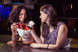 Young women toasting cocktail glasses at bar counter