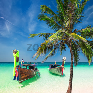 Amazing tropical beach with boats and palm tree. Thailand