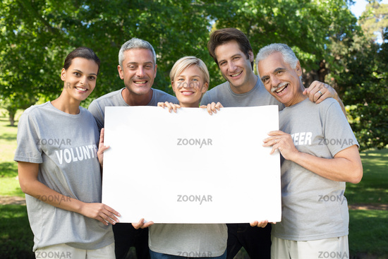 Happy volunteer family holding a blank