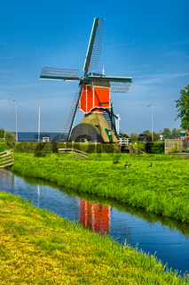 Windmills and water canal in Kinderdijk, Holland or Netherlands.