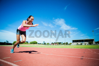 Female athlete running on the running track