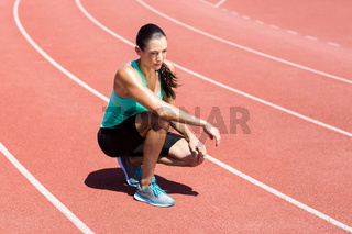 Female athlete kneeling on running track