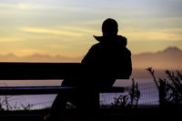 Silhouette of man on bench watching sunset