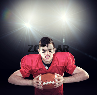 Composite image of american football player crushing a ball
