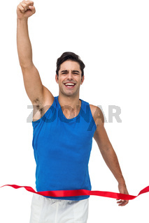 Portrait of cheerful winner athlete crossing finish line