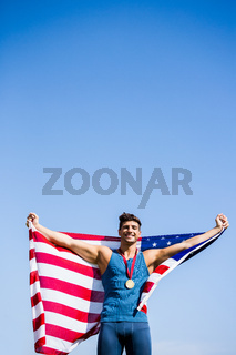 Athlete posing with american flag and gold medals around his neck