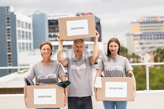 Smiling volunteers holding donation boxes