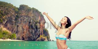 happy woman in bikini swimsuit with raised hands