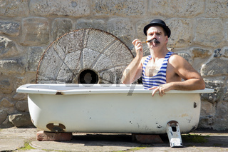 man with bowler hat smoking a pipe in the bath