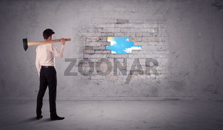 Business man hitting brick wall with hammer