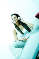 Young beautiful woman listening to music with a Tablet PC at home
