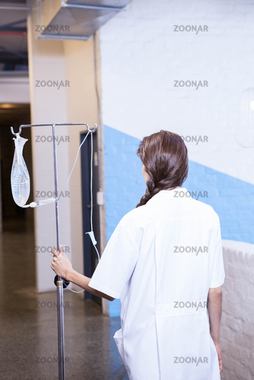 Female doctor carrying saline stand