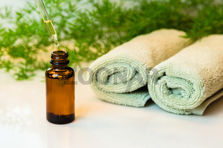 Bottle with essential oil, towels and greens on bathroom countertop
