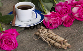 still life bouquet of roses, cup of black coffee, linking of cookies and one rose