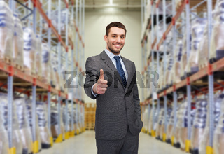 happy man at warehouse showing thumbs up gesture