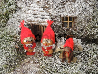 Christmas card - gnomes in front of their cosy home in the forest
