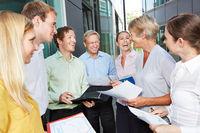 Lachende Geschäftsleute reden vor Büro