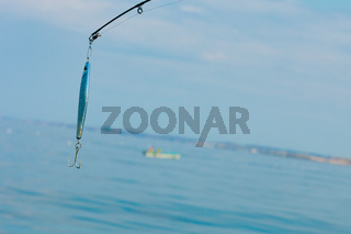 saltwater fishing - rod with wobbler and blue sea water