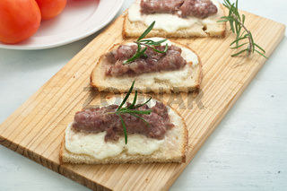 Crispy bruschetta topped with sausage and fresh rosemary