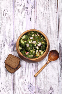 Okroshka with kvass in a wooden bowl and rye bread