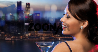 smiling woman holding cocktail over night city