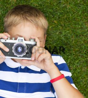 Happy smiling little boy with retro vintage camera