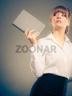 Pensive woman holding book. Education leisure.