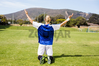 Rear view of female football player posing after a victory