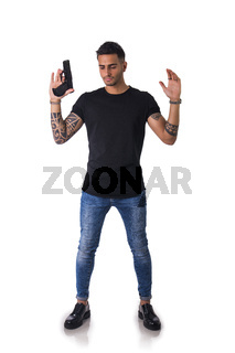 Handsome man with gun holding raised arms
