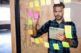 Man using digital tablet while writing on sticky notes