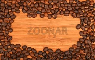 Coffee beans border frame over bamboo wood background