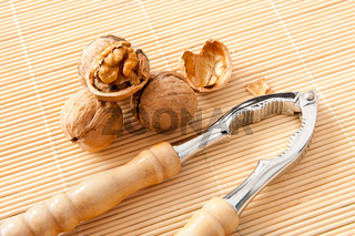 walnuts with broken shell and nutcracker