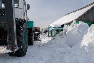 Winter time. Tractor cleans snow in village