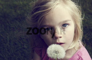 Portrait of caucasian blond girl blowing dandelion