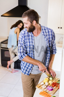 Man chopping vegetables and woman cooking on stove