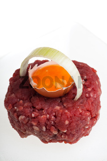 Steak Tartar mit Zwiebelring und offenem Ei