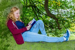 Dutch girl lying reading book in green tree