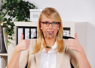 junge Frau sitzt mit gehobenem Daumen im Büro am Schreibtisch