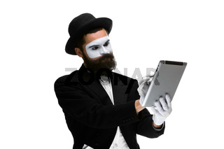 Man with a face mime working ona laptop