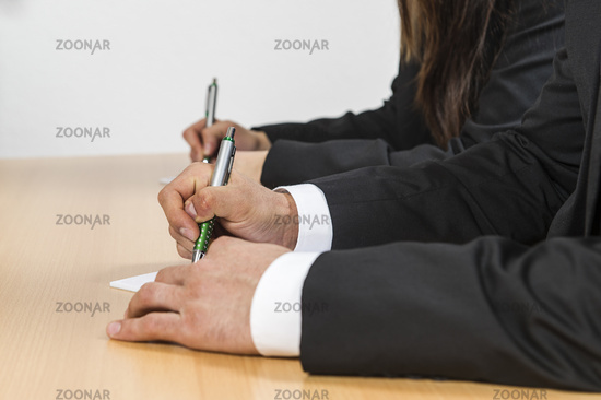 Hands with pen on a desk