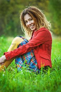 woman with dreadlocks sitting on grass