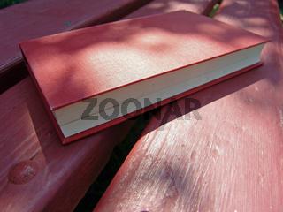 Buch liegt auf Sitzbank