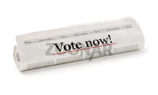 Rolled newspaper with the headline Vote now