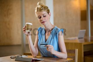 Beautiful woman having coffee while online shopping