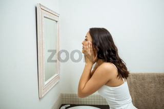 Woman checking her skin in bathroom