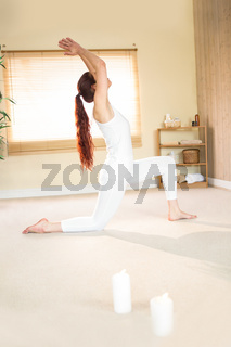 Full length of woman meditating with arms raised